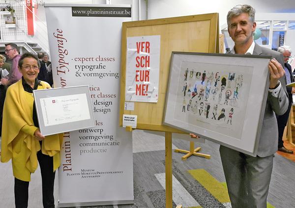 Kiki Douwes en Paul Adriaensen van het Plantin Instituut voor Typografie in Antwerpen poseren met de Typografie-prijs voor de Cayman Scheurkalender. De vertegenwoordiger van Cayman was verhinderd voor de prijsuitreiking.